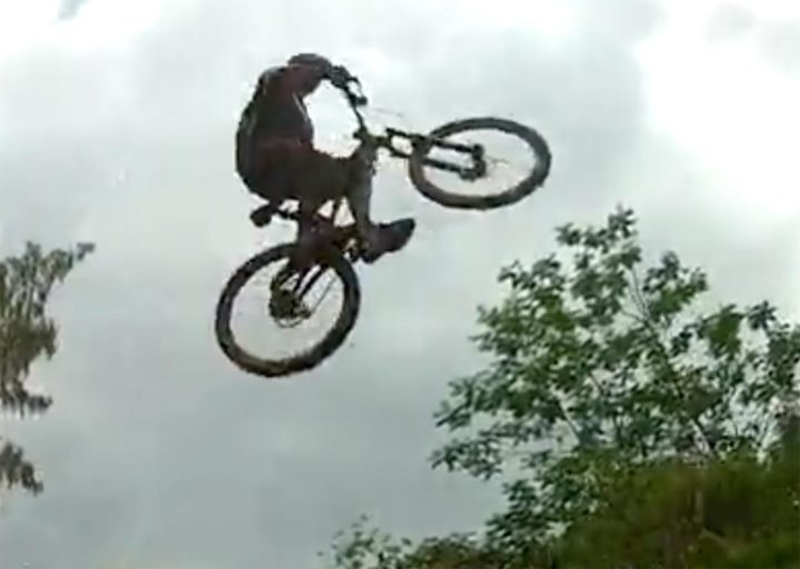 still photo from video: trail cyclist getting big air on a jump