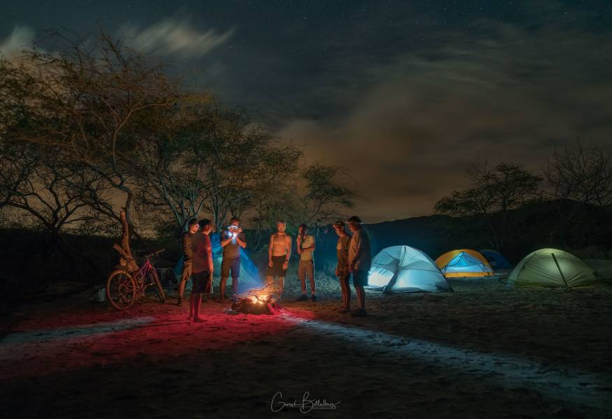 photo: nighttime campsite, tents illuminated from within. Bicycling tours in Hawaii.